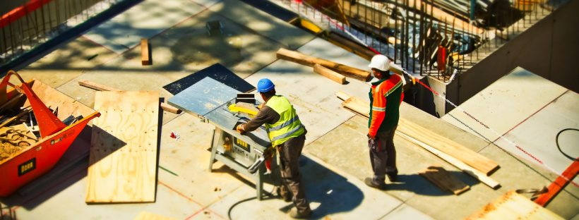 Image of two roofing contractors cutting wood on a construction site.